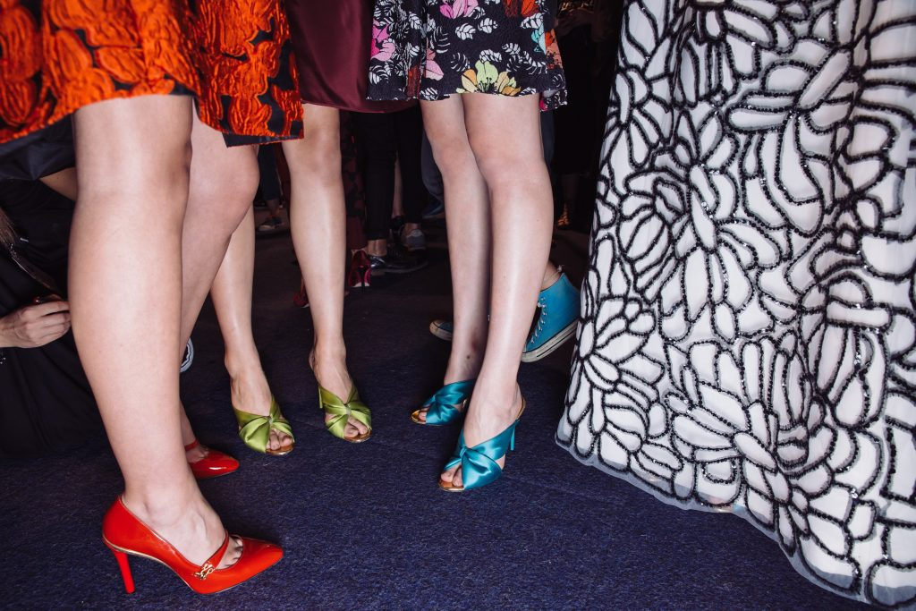 Several pairs of women' legs with multi coloured shoes