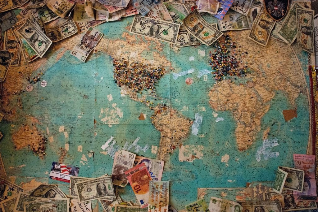 A map of the world with pins in and different world currencies