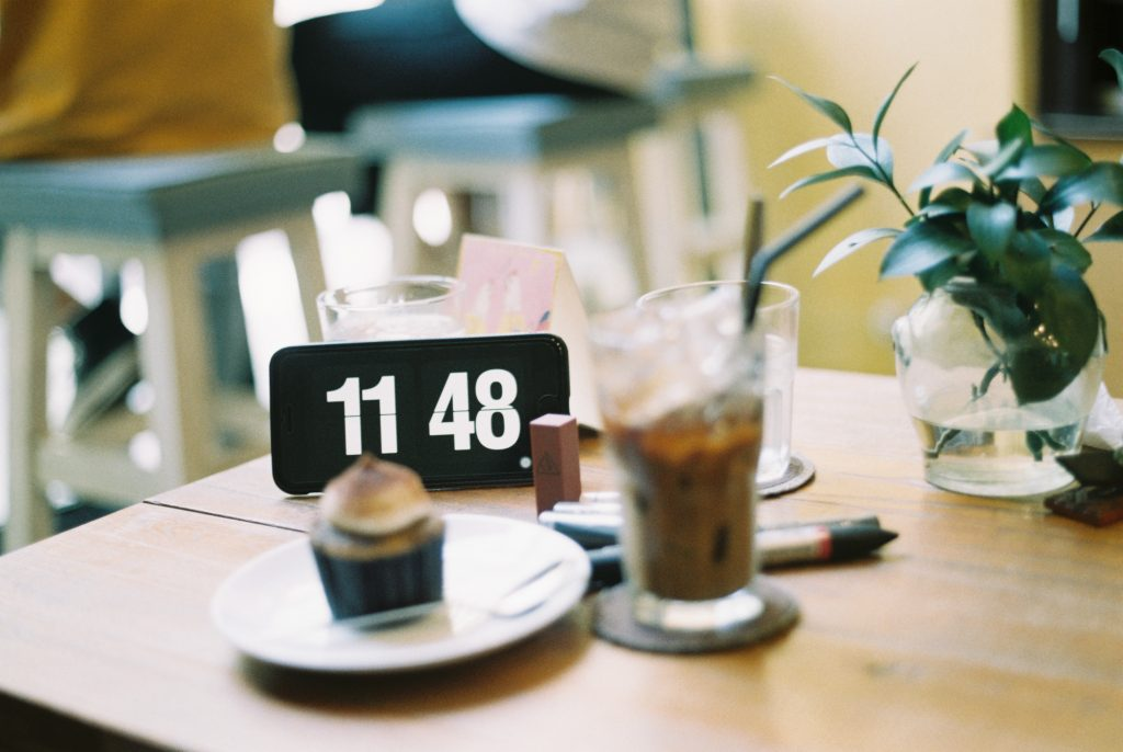 In Email Marketing Timing is Everything - A clock next to an iced coffee and muffin