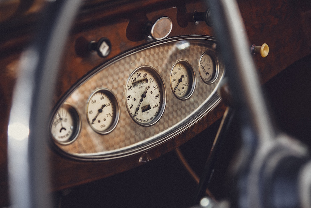 Dashboard in a vintage car showing dials and screens
