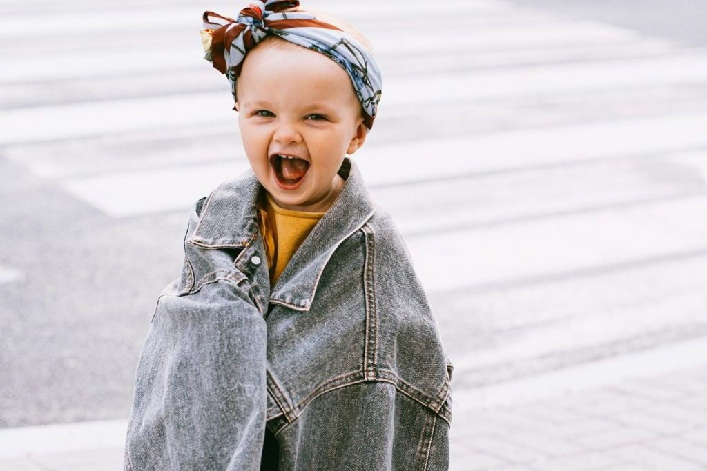 smiling baby in oversize denim jacket